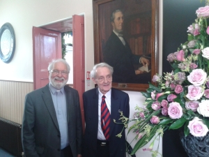 Rev Colin Campbell (left) and Rev Bill McMIllan in front of the portrait of Rev C.J. McAlester, in the vestibule of the church